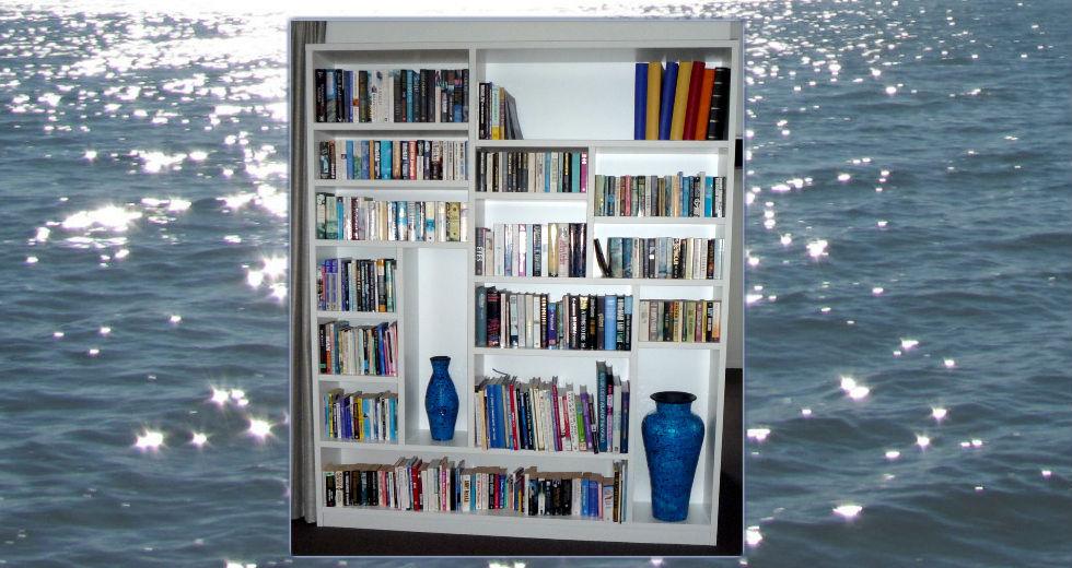 Custom white bookcase with varied shelves, books and vases