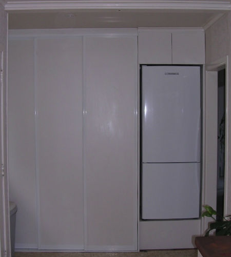 Custom laundry storage solution in a Thames kitchen. Includes full sliding doors so the laundry is hidden from view.