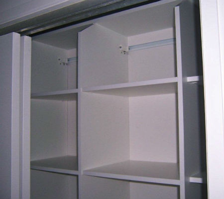 Top shelf of wardrobe specially cut to create easy access to storage space