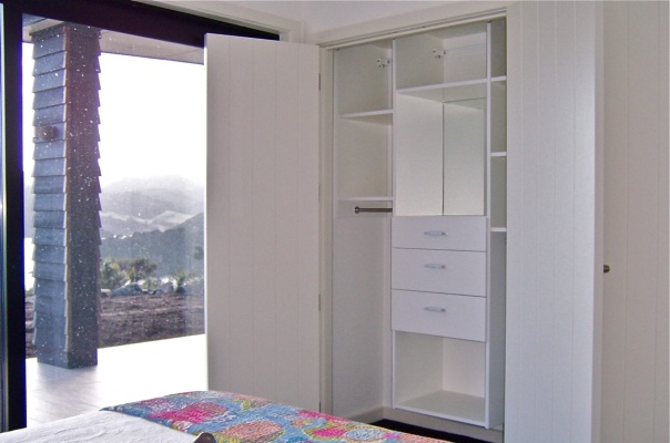 Wardrobe with built-in mirror and views of mountains outside Coromandel town